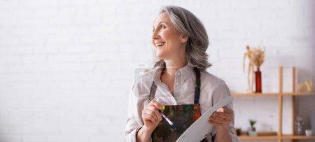 Lächelnde reife Frau in Schürze, Pinsel und Palette in der Hand, während sie wegschaut, Banner