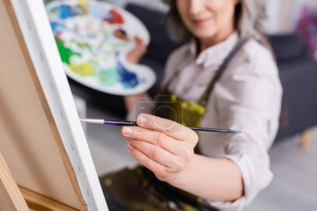 partial view of mature woman holding paintbrush while painting on canvas with blurred foreground
