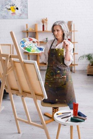 artista maduro sosteniendo pincel y paleta mientras está de pie cerca de lienzo