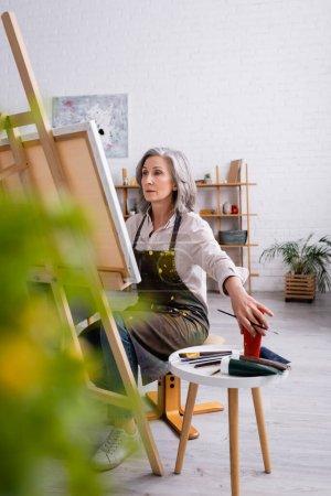 artista maduro sosteniendo pincel y alcanzando la pintura en tubo mientras está sentado cerca de la lona