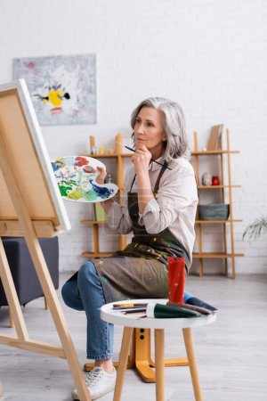 pensive mature artist holding paintbrush and palette while sitting near canvas