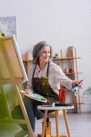 Photo pour Heureux artiste mature tenant pinceau et palette tout en atteignant la peinture bleue en tube et assis près de la toile - image libre de droit
