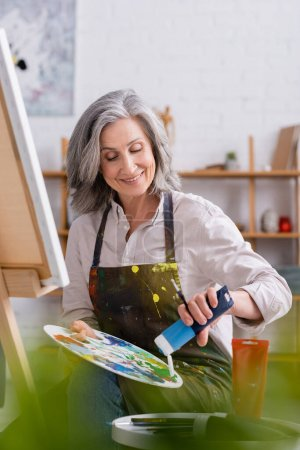 happy mature artist pouring blue paint on palette while sitting near canvas