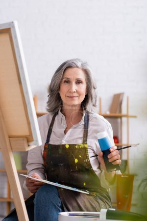 mature artist holding tube with blue paint and palette while sitting near canvas