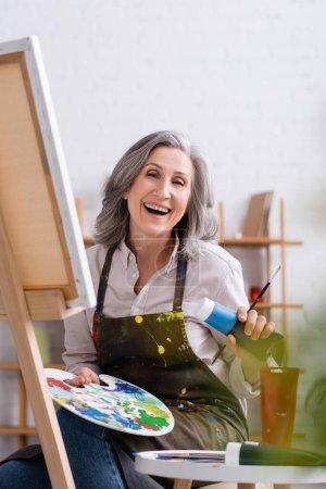feliz artista maduro sosteniendo tubo con pintura azul y paleta mientras está sentado cerca de la lona