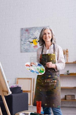 Photo pour Positif femme d'âge moyen tenant pinceau et palette avec des peintures colorées près du chevalet - image libre de droit