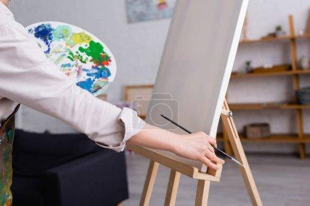 vista parcial de la mujer de mediana edad sosteniendo pincel y paleta con pinturas de colores cerca de lienzo en blanco