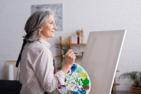 pleased middle aged woman holding paintbrush and palette with colorful paints near blank canvas