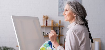 Photo for Pleased middle aged woman holding paintbrush and palette with colorful paints near blank canvas, banner - Royalty Free Image