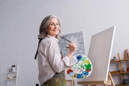 alegre mujer de mediana edad sosteniendo pincel y paleta con pinturas de colores cerca de lienzo en blanco
