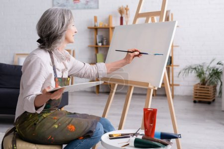 Photo for Cheerful middle aged woman holding paintbrush and palette while painting on canvas - Royalty Free Image