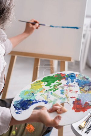 cropped view of middle aged woman holding palette and paintbrush while painting on canvas
