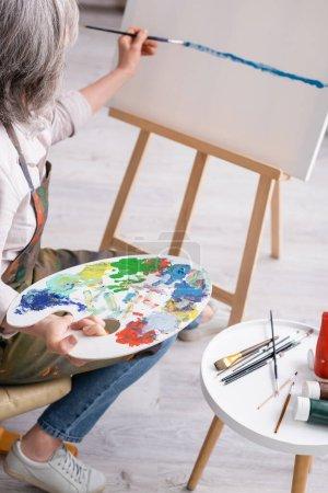 Photo pour Femme mature tenant palette et pinceau et peinture sur toile - image libre de droit