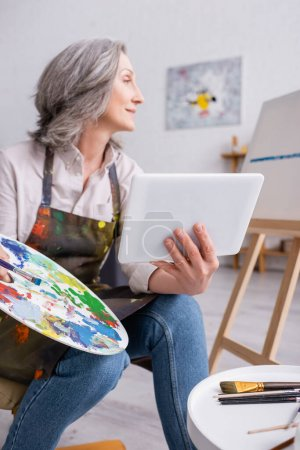 mature woman holding palette and digital tablet while looking at canvas