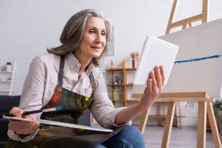 mujer madura sosteniendo paleta y tableta digital mientras mira tutorial cerca de lienzo