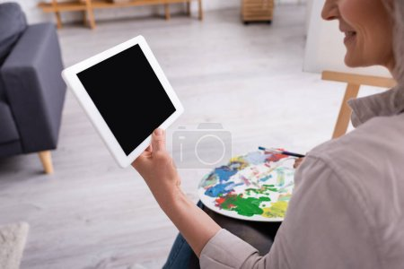Photo for Cropped view of happy mature woman holding palette and digital tablet with blank screen - Royalty Free Image