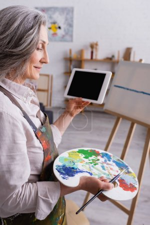 Photo for Mature woman holding palette, paintbrush and digital tablet with blank screen near canvas on blurred background - Royalty Free Image