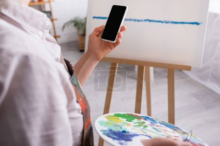 partial view of mature woman holding palette, paintbrush and smartphone with blank screen near canvas on blurred background
