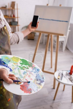 Photo for Cropped view of mature woman holding palette, paintbrush and smartphone with blank screen near canvas on blurred background - Royalty Free Image