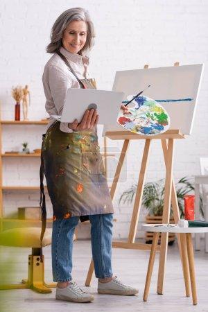 Photo pour Heureuse femme mature tenant palette et ordinateur portable tout en regardant tutoriel près de toile - image libre de droit