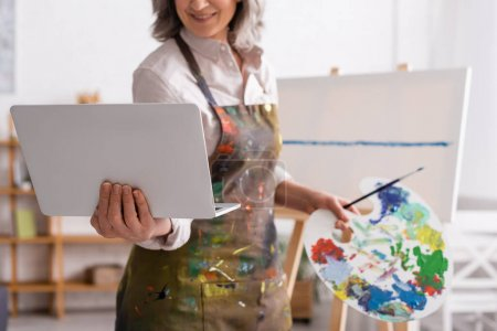 cropped view of mature woman holding palette and laptop while watching tutorial near canvas