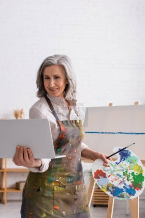 sonriente mujer madura sosteniendo paleta y portátil mientras mira tutorial cerca de lienzo