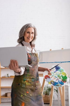 joyful mature woman holding palette and laptop near canvas