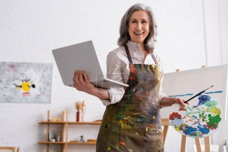 Photo for Positive mature artist holding palette and laptop while watching tutorial near canvas - Royalty Free Image