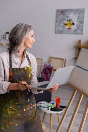 Photo for Mature woman holding paintbrush and laptop while looking at canvas - Royalty Free Image