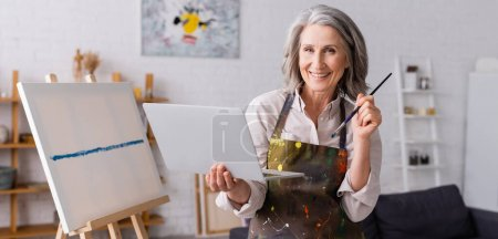 happy mature artist holding paintbrush and laptop near canvas, banner