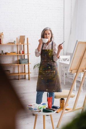 Photo pour Artiste d'âge moyen tenant tasse de café et pinceau tout en regardant la toile - image libre de droit