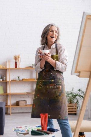 Photo pour Excité artiste d'âge moyen tenant tasse de café et pinceau près de la toile - image libre de droit