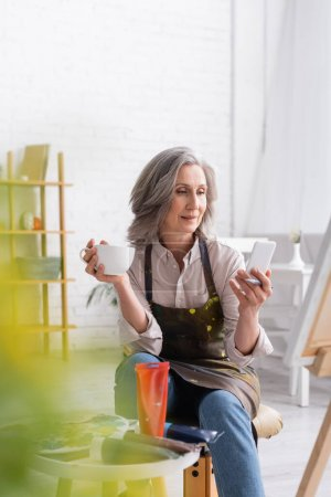 Photo for Middle aged artist holding paintbrush, cup of coffee and using smartphone near canvas and blurred foreground - Royalty Free Image