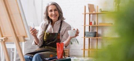 feliz artista de mediana edad sosteniendo pincel, taza de café y el uso de teléfono inteligente cerca de la lona y borrosa primer plano, pancarta