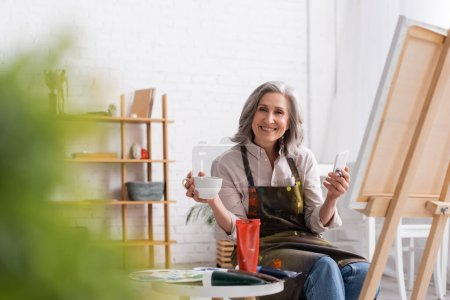 happy middle aged artist holding paintbrush, cup of coffee and using smartphone near canvas and blurred foreground