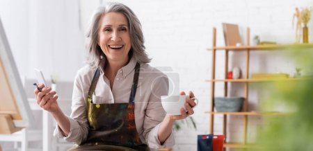 happy middle aged artist holding paintbrush, cup of coffee and using smartphone near canvas, banner