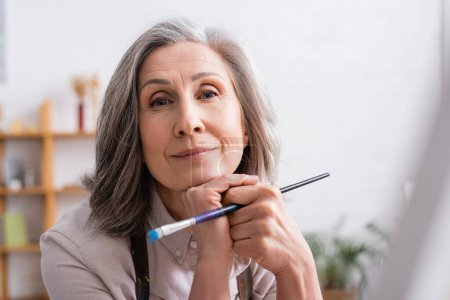 Photo for Middle aged artist with grey hair holding paintbrush - Royalty Free Image