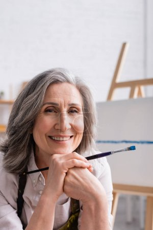 joyful middle aged painter with grey hair holding paintbrush