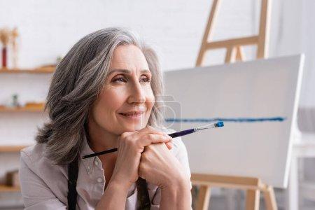 Photo pour Heureux peintre d'âge moyen avec les cheveux gris tenant pinceau tout en regardant loin - image libre de droit