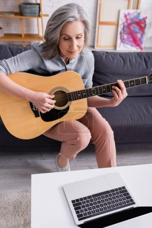 middle aged woman with grey hair learning to play acoustic guitar near laptop with blank screen on coffee table