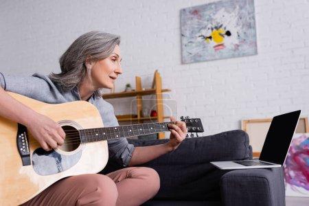 femme d'âge moyen avec les cheveux gris apprenant à jouer de la guitare acoustique près d'un ordinateur portable avec écran blanc sur le canapé