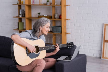 Photo for Happy middle aged woman with grey hair learning to play acoustic guitar near laptop on sofa - Royalty Free Image