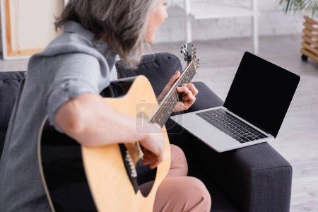 verschwommene Frau mittleren Alters lernt Akustikgitarre in der Nähe von Laptop mit leerem Bildschirm auf Sofa zu spielen