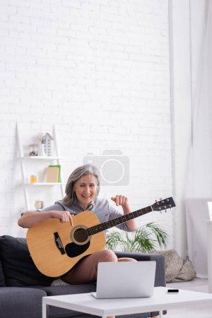 Photo pour Femme d'âge moyen avec les cheveux gris pointant vers la guitare acoustique pendant l'appel vidéo sur ordinateur portable - image libre de droit