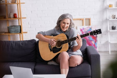 amazed middle aged woman with grey hair learning to play acoustic guitar near laptop