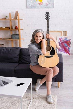 Photo pour Femme mature avec les cheveux gris tenant guitare acoustique tout en étant assis sur le canapé près de gadgets dans le salon - image libre de droit