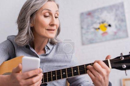 Photo pour Femme mature avec les cheveux gris tenant smartphone flou tout en apprenant à jouer de la guitare acoustique - image libre de droit