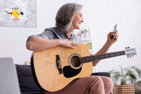 Photo pour Femme mûre souriante avec les cheveux gris tenant smartphone tout en apprenant à jouer de la guitare acoustique - image libre de droit