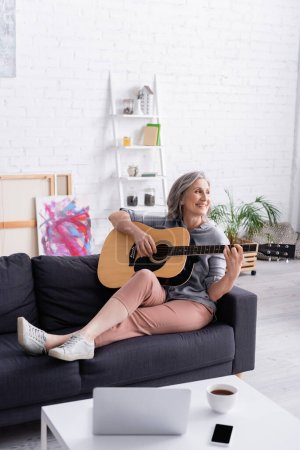 happy middle aged woman playing acoustic guitar near gadgets and cup of tea on coffee table