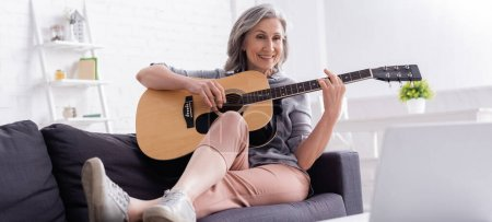 cheerful middle aged woman playing acoustic guitar on couch near laptop, banner